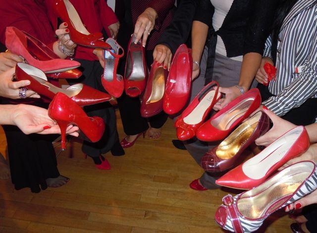 Manos mostrando zapatos distintos rojos