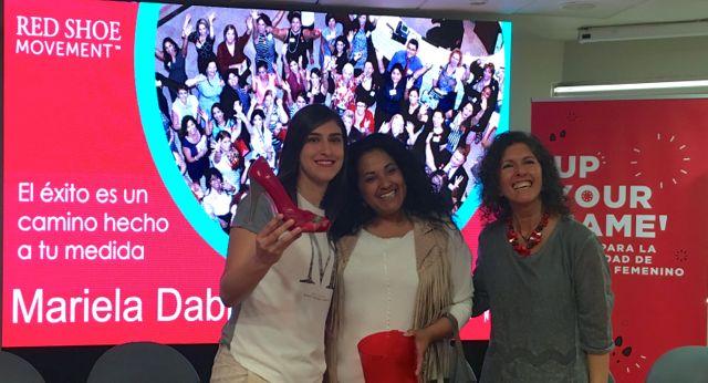 Paola Peña, dueña de Calzados Piel Canela, entrega zapatos a la ganadora del sorteo del evento que el Red Shoe Movement realizó en Coca-Cola Chile.